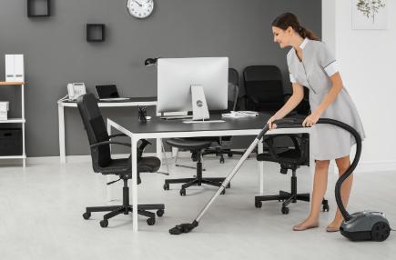 Schoonmaakbedrijf Amsterdam, een vrouwelijke personeel die bij een kantoor aan het stofzuigen is.