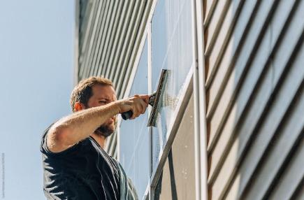 Schoonmaakbedrijf Amsterdam, een glazenwasser bezig met de glasbewassing