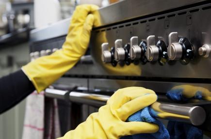 Schoonmaakbedrijf Amsterdam, een schoonmaker die het fornuis + de oven aan het reinigen is.